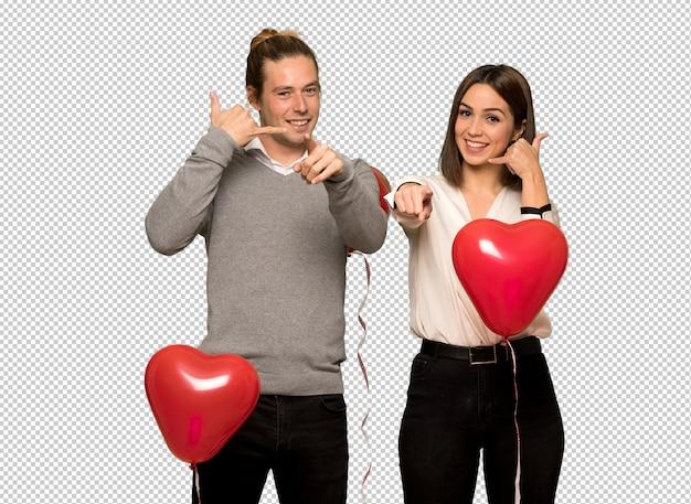 Paar dat in valentijnskaartdag telefoongebaar maakt en voorzijde richt