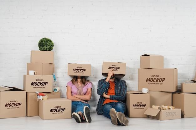 Paar dwaas poseren met verhuisdozen boven hun hoofd