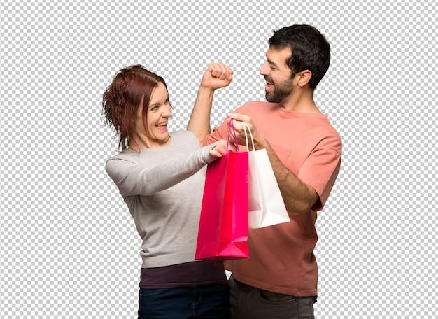 Paar in valentijn dag houden boodschappentassen in overwinning positie