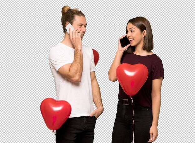 Paar in valentijnskaartdag die een gesprek met de mobiele telefoon houden