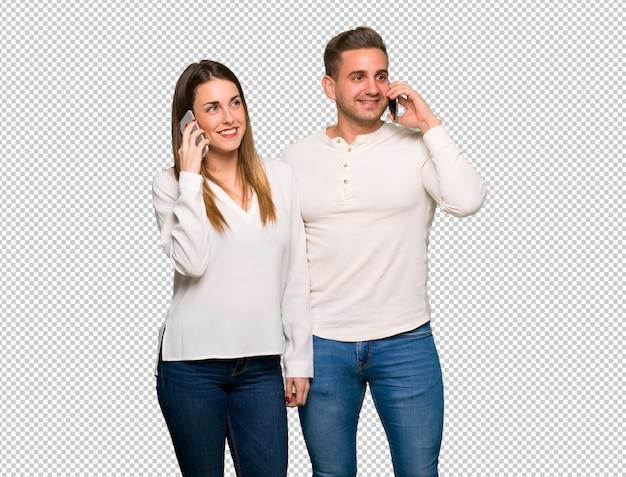 Paar in valentijnskaartdag die een gesprek met de mobiele telefoon houdt
