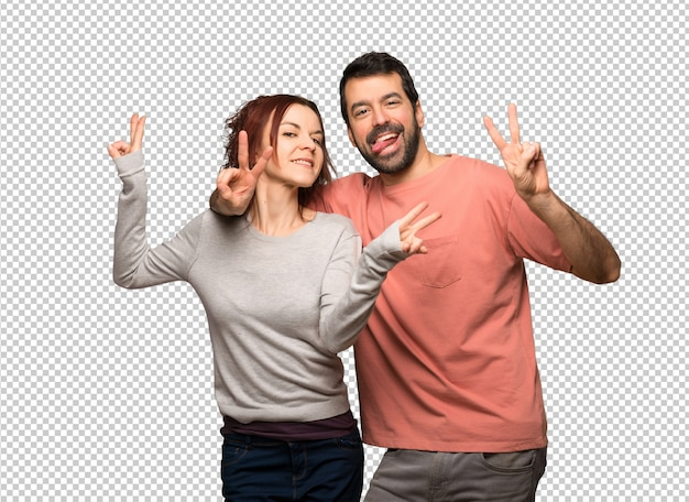 Paar in valentijnskaartdag die en overwinningsteken glimlacht toont