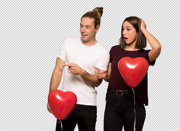 Paar in valentijnskaartdag die vinger aan de kant met een verrast gezicht richten