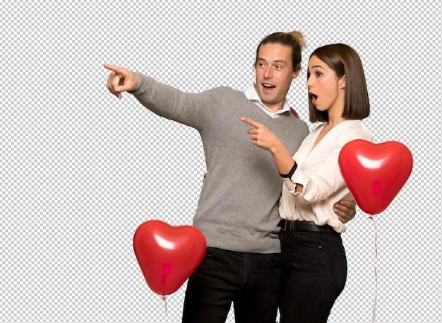 Paar in valentijnskaartdag die vinger aan de kant richten en een product voorstellen