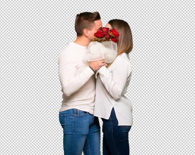 Paar in valentijnskaartdag met bloemen en het kussen