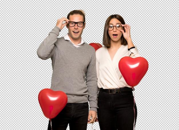 Paar in valentijnskaartdag met glazen en verrast