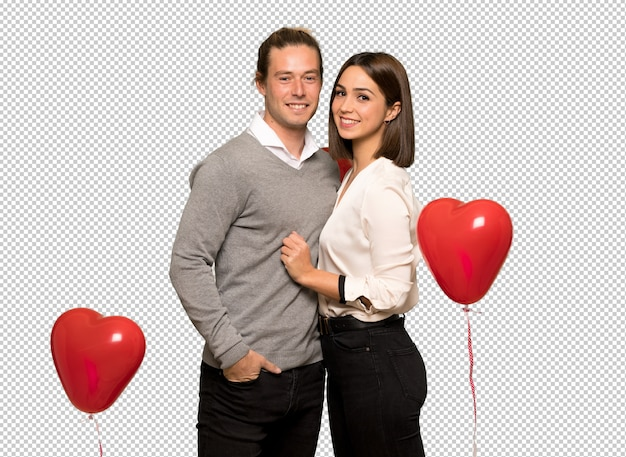 Paar in valentijnskaartdag stellen met wapens bij heup en het glimlachen