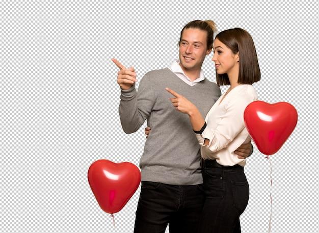 Paar in valentijnskaartdag wijzende vinger aan de kant in zijpositie