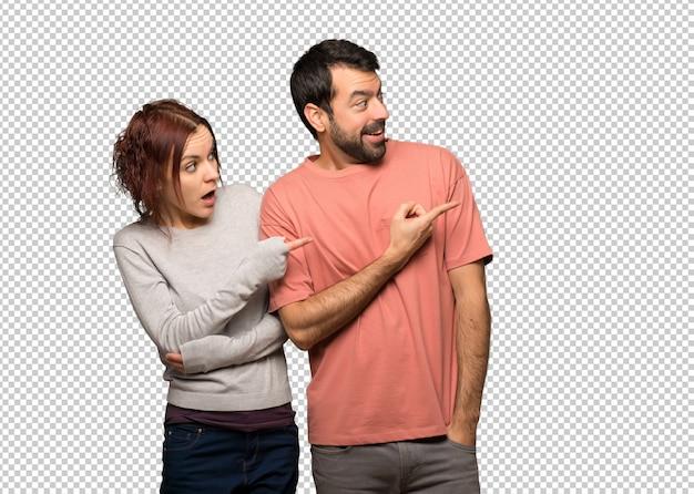 Paar in valentijnskaartdag wijzende vinger aan de kant met een verrast gezicht