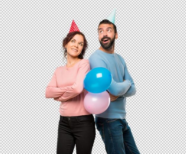 Paar met ballons en verjaardagshoeden die omhoog terwijl het glimlachen kijken