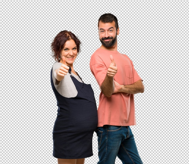 Paar met zwangere vrouw die duimen op gebaar en het glimlachen geeft