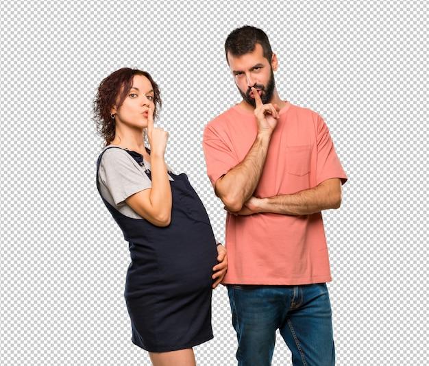 Paar met zwangere vrouw die een teken van het sluiten van mond en stiltegebaar toont