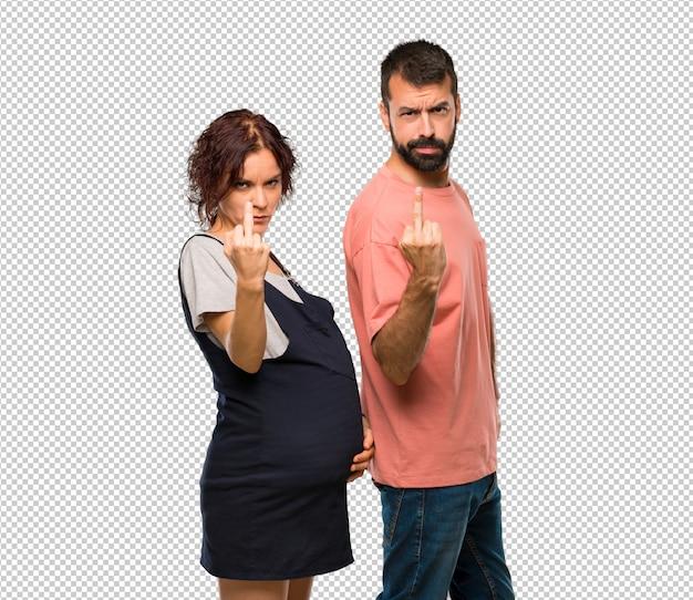 Paar met zwangere vrouw die hoorngebaar maakt. negatieve expressie