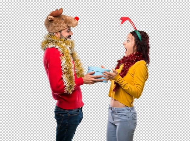 Paar verkleed voor de kerstvakantie met een cadeautje