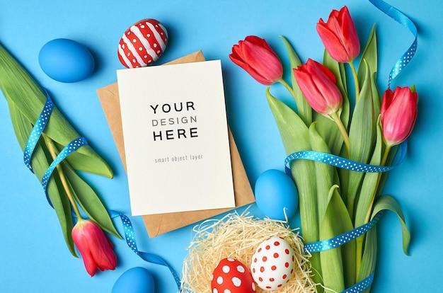 Paasvakantie wenskaart mockup met gekleurde eieren en rode tulp bloemen