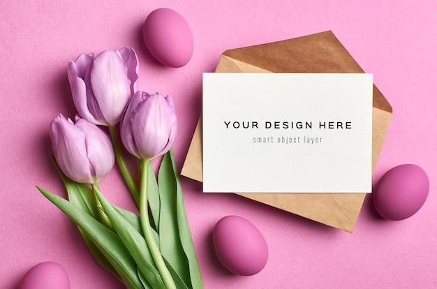Paasvakantie wenskaart mockup met gekleurde eieren en tulpen op roze