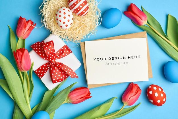 Paasvakantie wenskaart mockup met gekleurde eieren, geschenkdoos en rode tulp bloemen
