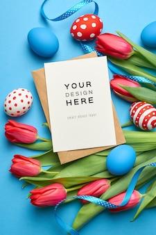 Paasvakantie wenskaart mockup met gekleurde eieren, linten en tulp bloemen