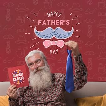Padre sosteniendo corbata y maqueta de cartón sobre fondo burdeos