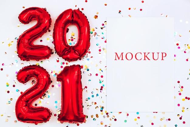 Palloncini rossi a forma di numeri 2021 e mockup di carta