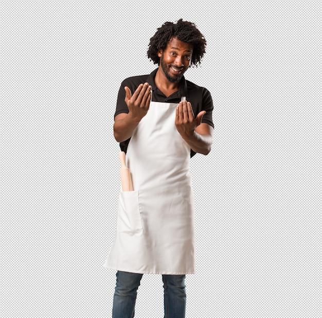 Panettiere afroamericano bello che invita a venire, sicuro e sorridente facendo un gesto con la mano, essendo positivo e amichevole