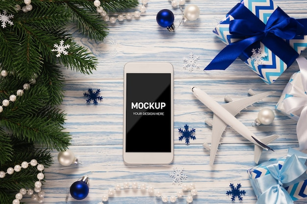 Pantalla de maqueta de smartphone con modelo de avión entre adornos navideños
