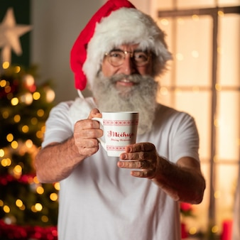 Papá noel barbudo sosteniendo una taza