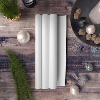 Papel en blanco sobre mesa de madera rodeada de adornos y pinos