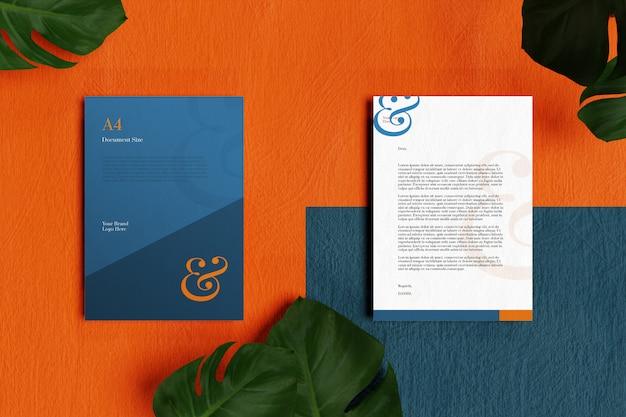 Papel con membrete a4 y maqueta de papelería en piso naranja y azul