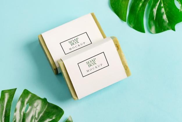 Paquete de dos maquetas de caja de envoltura de jabón con barra de jabón de oliva aislado sobre fondo azul con hojas de palma