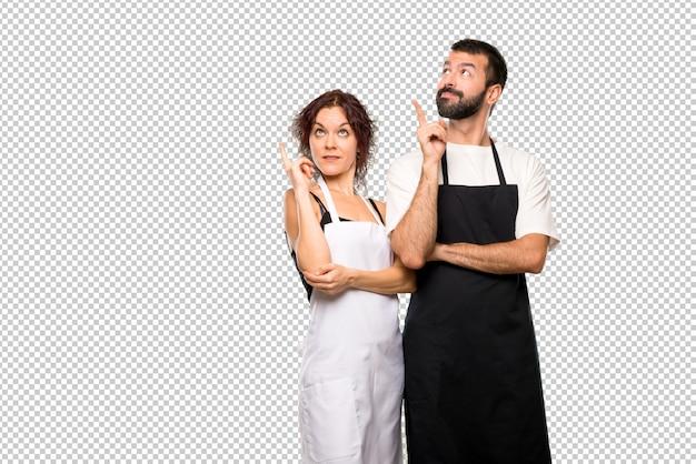 Par de cocineros apuntando con el dedo una gran idea y mirando hacia arriba