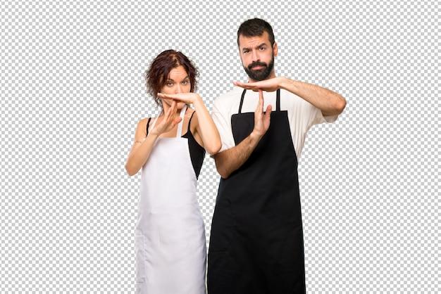 Par de cocineros haciendo parada gesto con la mano para detener un acto