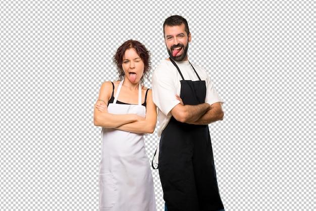 Par de cocineros mostrando la lengua en la cámara con aspecto divertido
