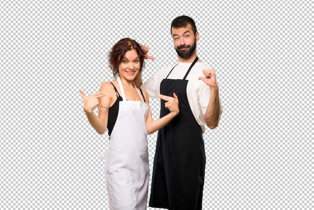 Par de cocineros orgulloso y satisfecho de sí mismo en el mismo concepto