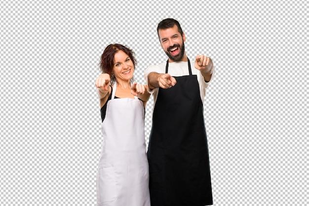 Pareja de cocineros señala con el dedo mientras sonríe