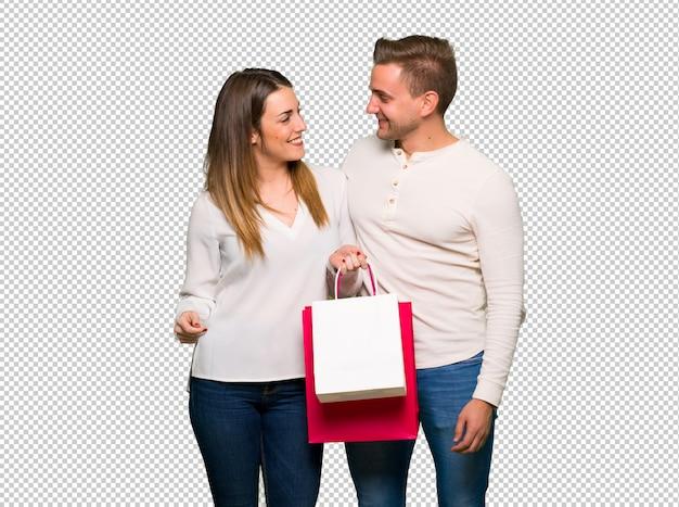 Pareja en el día de san valentín con bolsas de compras en posición de victoria