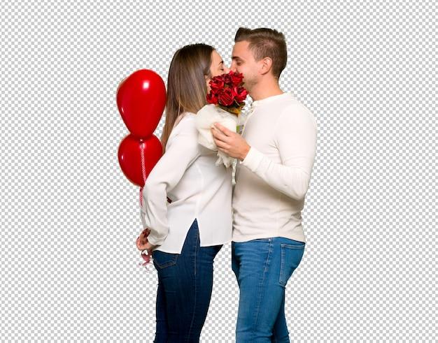 Pareja en el día de san valentín con flores y globos con forma de corazón