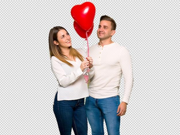 Pareja en el día de san valentín con globos con forma de corazón