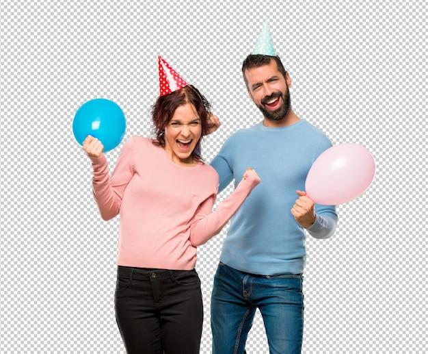 Pareja con globos y sombreros de cumpleaños celebrando una victoria y feliz por haber ganado un premio