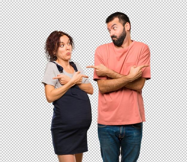 Pareja con mujer embarazada apuntando a los laterales teniendo dudas. persona indecisa