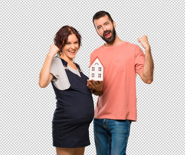 Pareja con mujer embarazada sosteniendo una casita