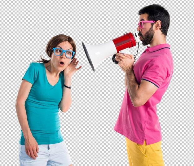 Pareja en ropa colorida gritando por megáfono