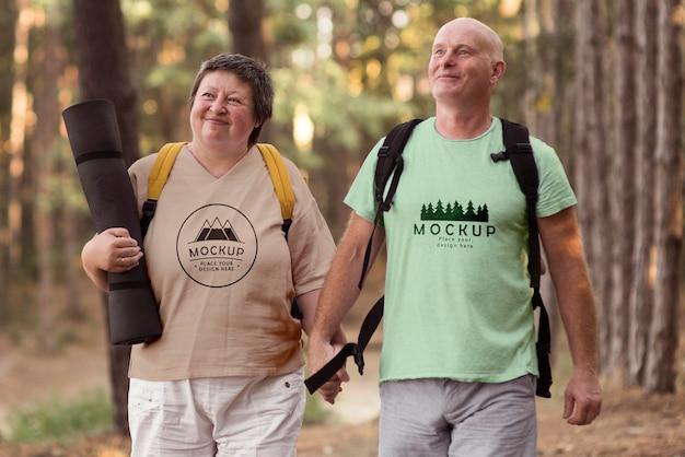 Pareja senior en camping con una camiseta de maqueta