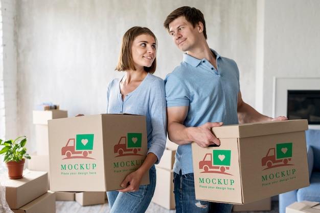 Pareja sosteniendo cajas para su nuevo hogar y mirarse