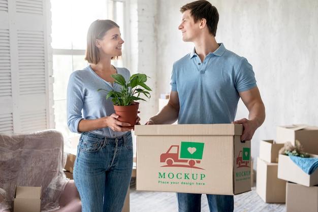 Pareja sosteniendo plantas y caja con objetos para su nuevo hogar