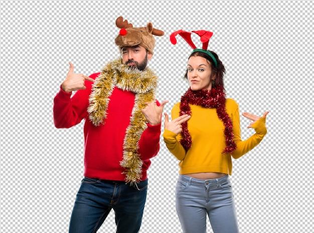Pareja vestida para las fiestas navideñas orgullosa y satisfecha de ti misma en el concepto de amor