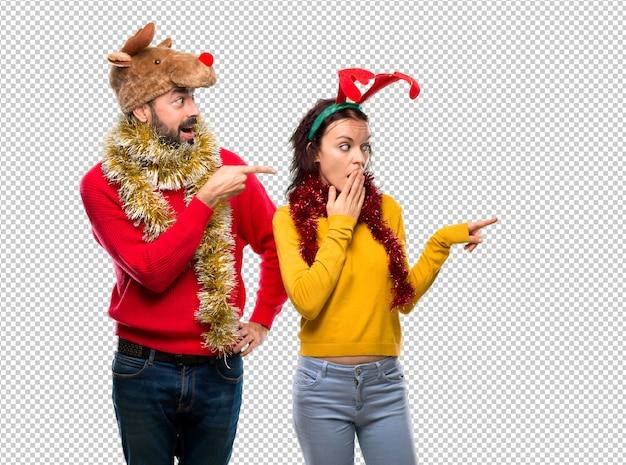 Pareja vestida para las vacaciones de navidad apuntando con el dedo hacia un lado con una cara sorprendida