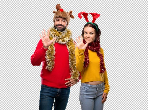 Pareja vestida para las vacaciones de navidad contando cinco con los dedos