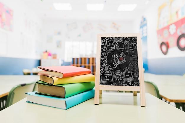 Pequeña maqueta de pizarra junto a coloridos libros