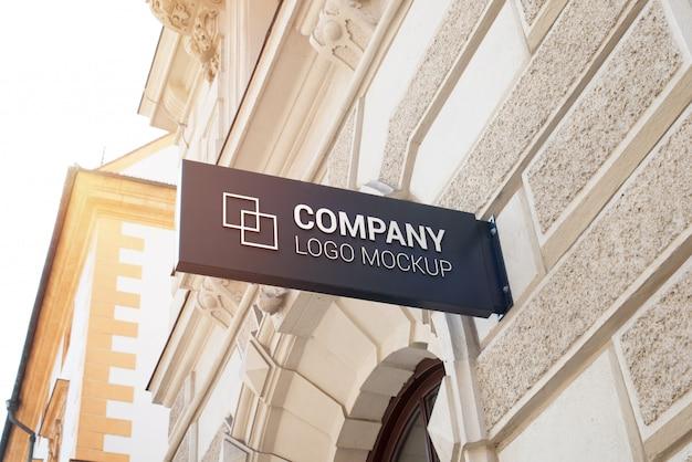 Pequeño cartel rectangular con maqueta del logotipo de la empresa en la pared del edificio del centro de la ciudad moderna